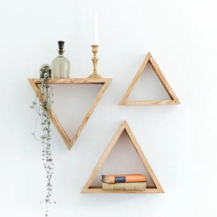 drei Wandregale in Dreiecksform nebeneinander mit Büchern und Getränken darauf