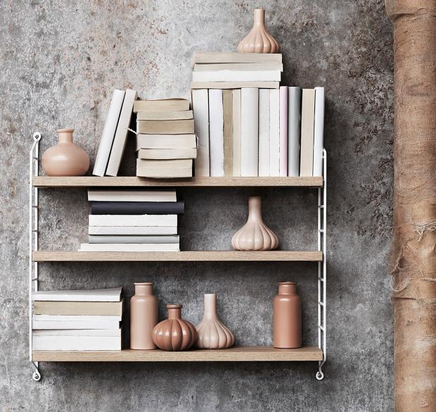Wandregal mit Büchern auf grauer Wand