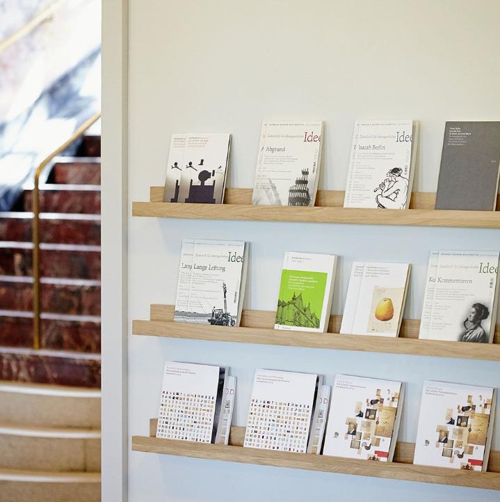 drei Wandregale mit jeweils 4 Büchern auf Wand montiert, dahinter Stiegenaufgang
